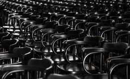 Lot of black wooden chairs stand in a diagonal. In a large room Royalty Free Stock Image