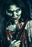 Lot of blood. Bloodthirsty zombi with a knife standing at the night cemetery in the mist and moonlight Royalty Free Stock Image