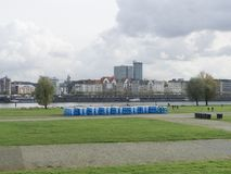 Blue bio toilets on the green embankment of the river stock image
