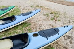 A lot of blue and green canoe kayaks with front parts of the noses for water sports, swimming lie on the beach on the beach royalty free stock photography