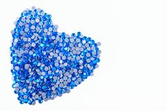A lot of blue rhinestones made in the shape of a heart on a white background. Top view. Royalty Free Stock Photo