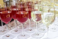 Lot of blurred glasses with red and white wine on the reception party table.  stock photo