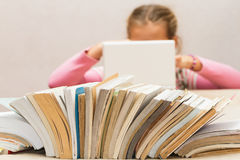 Lot of books and a girl with a laptop. Royalty Free Stock Image