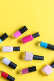 Lot of bottles nail polish on yellow background top view Royalty Free Stock Photo