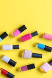 Lot of bottles nail polish on yellow background top view Stock Photo
