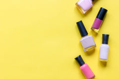 Lot of bottles nail polish on yellow background top view royalty free stock image