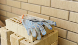 A lot of bricks and gloves are ready to be used for work. Royalty Free Stock Images