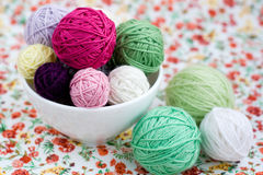 A lot of bright balls of knitting on the background of a flower. A lot of bright balls of knitting on the background of a red flower stock photo