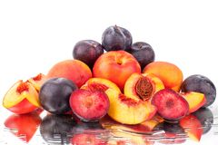 A lot of bright fruits, whole and cut peaches and plums on a mirror white background in water drops isolated. Close up royalty free stock images