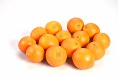 Lot of bright orange orange lie in a bunch on a white background, raw material for an orange fresh. Stock Photo