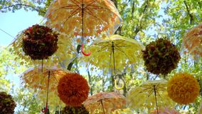 Lot of brightly orange and yellow umbrellas and balls hanging and moving in the wind in autumn park. Lot of brightly orange and yellow umbrellas and balls stock video footage