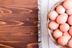 A lot of brown eggs in a wicker basket on a brown table top view Royalty Free Stock Photo