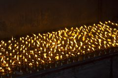 A lot of burning oil candles standing in the dark royalty free stock image