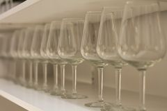 Lot clear wine glasses on high leg  in row  on rack sell in the store. Or supermarket Royalty Free Stock Photo