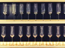 Lot clear wine glasses on high rack in row on rack in the store or supermarket. Empty glasses on shelf in restaurant. Lot clear wine glasses on high rack in row Royalty Free Stock Photos