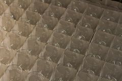 Lot clear wine glasses stored in a cardboard box in the warehouse Stock Image