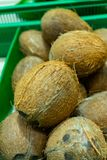A lot coconuts in the supermarket. Many coco lying in a boxes royalty free stock photos