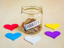 A lot of coins and charity word in a glass jar near five colorful hearts. Saving and collecting money for charity stock photo