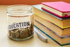 A lot of coins and education word in a glass jar near a white ballpoint pen and few books on a table. Saving money for education royalty free stock photos