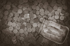 A lot of coins and a glass jar Stock Photos