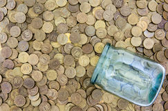 A lot of coins and a glass jar Royalty Free Stock Image