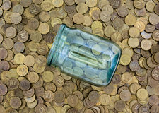 A lot of coins and a glass jar Stock Images