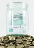 A lot of coins and a glass jar Royalty Free Stock Photo