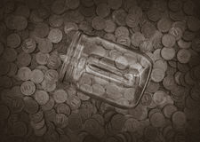 A lot of coins and a glass jar Royalty Free Stock Photography