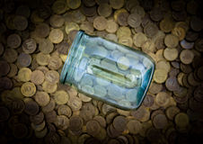 A lot of coins and a glass jar Stock Photo