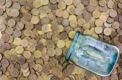 A lot of coins and a glass jar Royalty Free Stock Images
