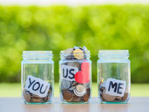 A lot coins in glass money jar on the wood table. Saving for family concept Stock Images