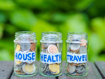 A lot coins in glass money jar. On the wood table. Saving for house, health and travel concept Royalty Free Stock Image