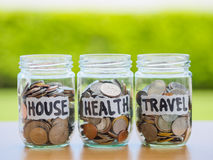 A lot coins in glass money jar on the wood table. Saving for house, health and travel concept Stock Image
