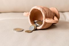 A lot of coins spill out of a clay Cup on a leather background Royalty Free Stock Photos
