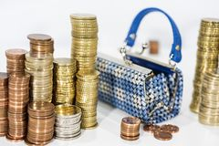 A lot of coins on white table with black purse. Royalty Free Stock Images