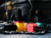 A lot of colored nail Polish and the jeans Royalty Free Stock Image