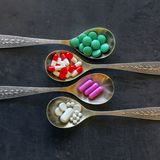 A lot of colored pills and medicines, vitamins, capsules in a spoon on a dark background. stock image