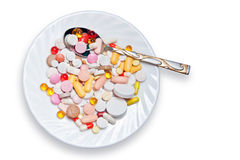 Lot of colored pills on plate and spoon. Isolated on white background Stock Photo
