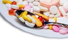 Lot of colored pills on plate and spoon Stock Images