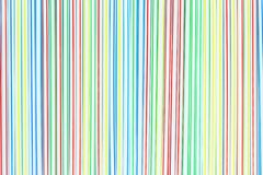 A lot of colored plastic straws or tubes with blue, red, yellow and green stripes. Abstract background royalty free stock image