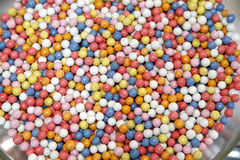 Lot of colored sweet dragees in jar. Heap of sugared colorful sweet dragees as a background stock photos