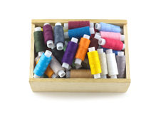 Colored spools with thread in wooden box isolated close up Stock Photo