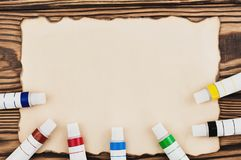 Lot of colorful acrylic paints in closed tubes on burnt rectangle blank paper. On old wooden brown boards. Top view stock image