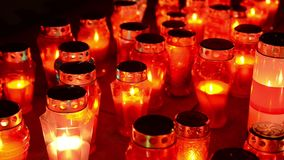 A lot of colorful candles burning at cemetery at night. Votive candles glows on grave. All saints day. Prayer lighted candles in a