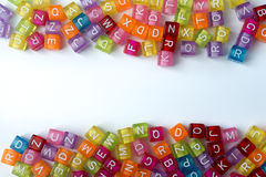 A lot of colorful cubes with letters on a white background. Many colorful decorative cubes with letters on a white background Stock Photo