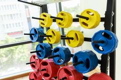 A lot of colorful dumbbell on stand stock photo
