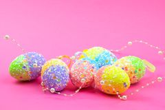 A lot of colorful Easter eggs on a pink background. Place for text. royalty free stock photos