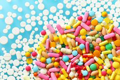 Colorful medecine pills on a blue background. A lot of colorful medecine pills on a blue background and white pills Stock Image