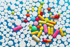 Colorful medecine pills on a blue background. A lot of colorful medecine pills on a blue background and white pills Royalty Free Stock Photos