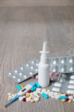Lot of colorful medication and pills from above on grey wooden background. All for flu - nasal spray, , vitamins, capsules, thermo Stock Image